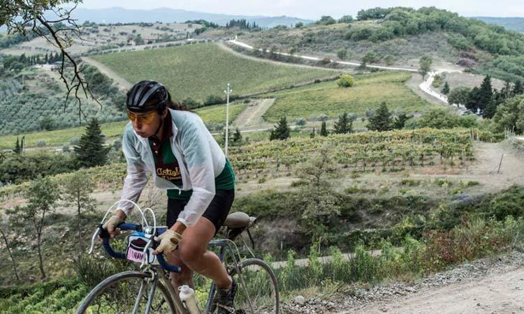 Una ciclista affronta una salita tra le colline toscane