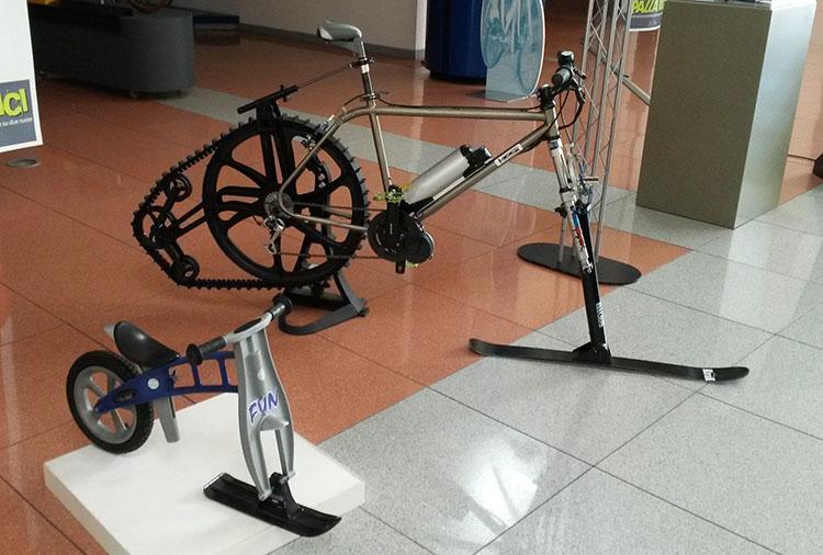 foto di una bici da bimbo e di una bici da neve con sci e cingolo posteriore