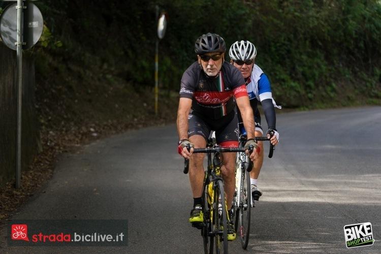 Immagine che mostra un ciclisti su bici da corsa, su strada, durante test di Bike Shop test