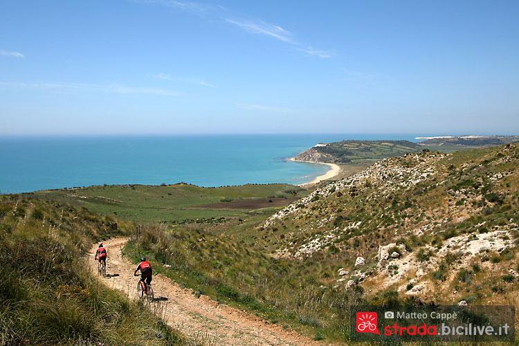 due cicloturisti affrontano un sentiero vicino al mare