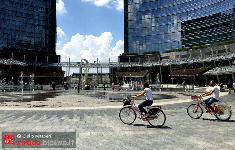 ciclisti pedalana in Piazza Gae Aulenti godendosi lo skyline di Milano
