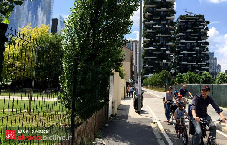 una famiglia pedala lungo una pista ciclabile vicino al bosco verticale