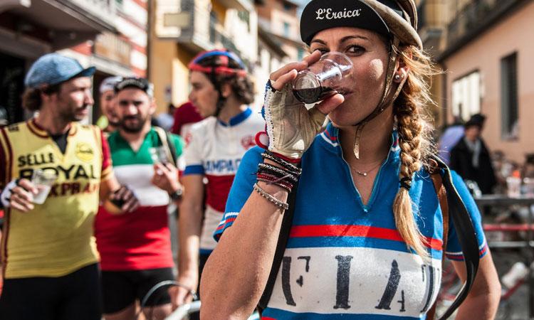 una ciclista si disseta e si diverte dopo la granfondo di ciclismo eroica