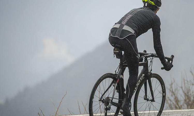 un ciclista pedala sotto la pioggia con abbigliamento invernale santini