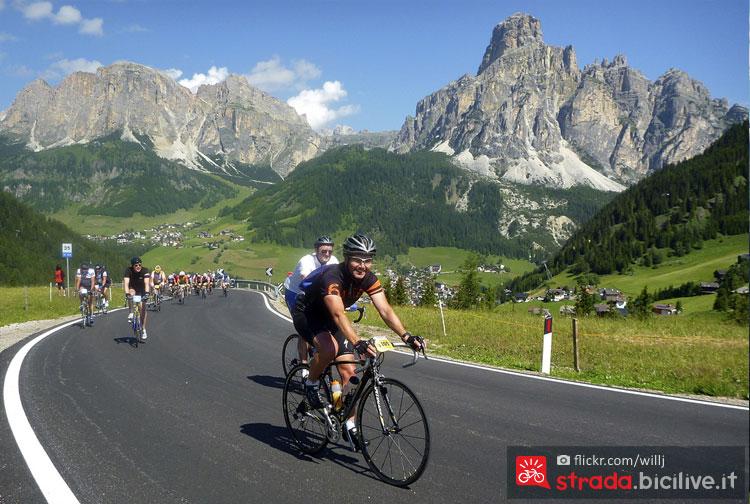 ciclista sale il passo campolongo con le dolomiti alle spalle