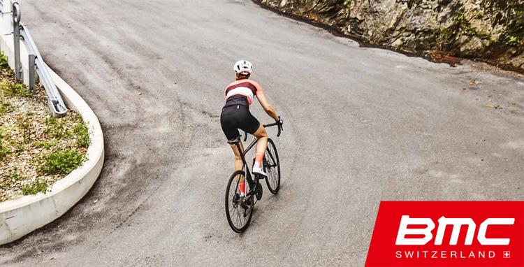 Ciclista pedala in salita su una bici da strada BMC del 2019