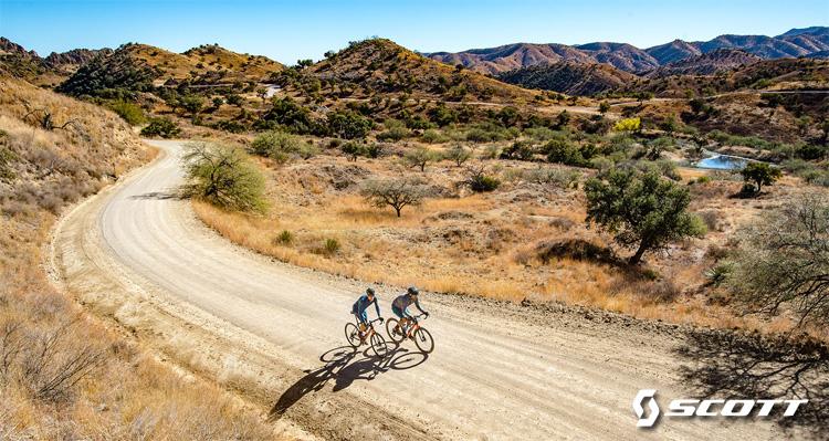 Coppia di ciclisti pedala su strada sterrata in sella a bici Scott