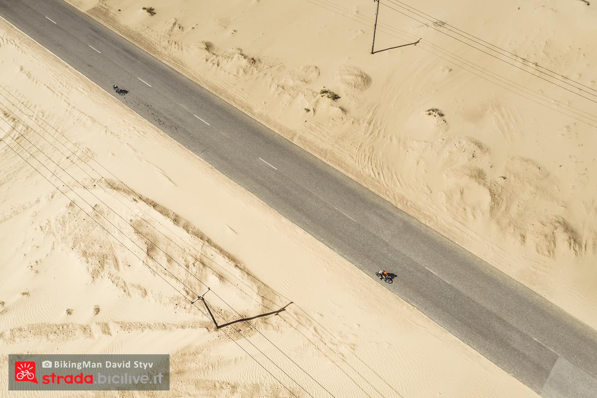Ciclisti pedalano in Oman circondati dal deserto durante il Biking Man 2019