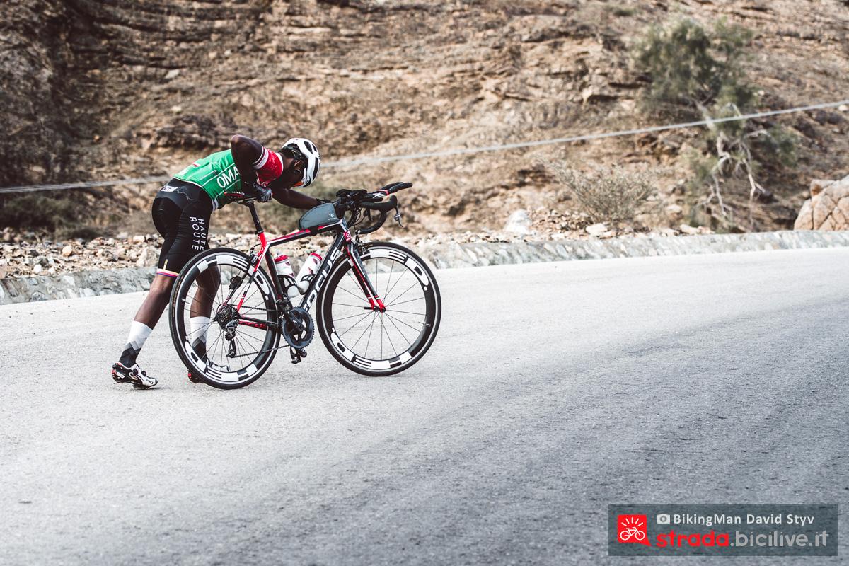 Ciclista solitario spinge la sua bicicletta in Oman durante il Biking Man 2019