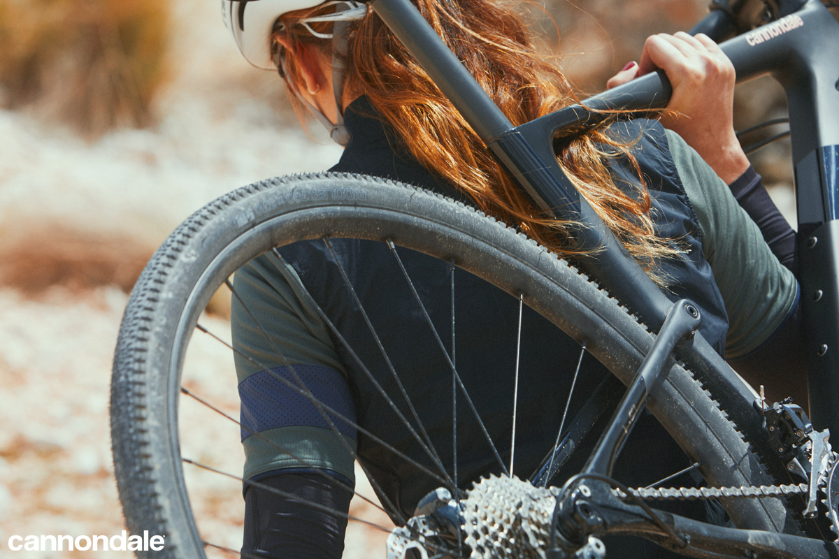 Ciclista donna porta in spalla una bici gravel Cannondale Topstone Carbon 2020