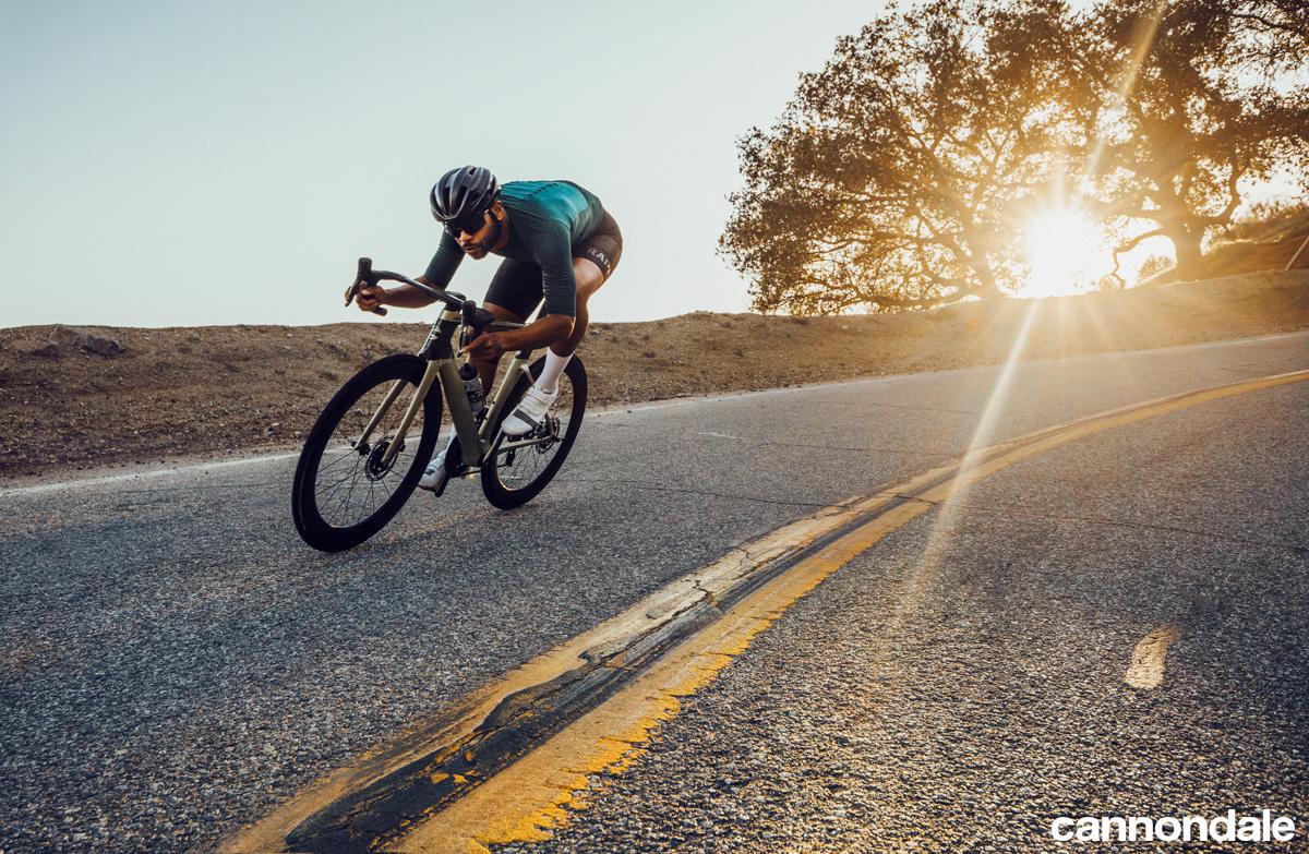 Ciclista su asfalto in sella a bici Cannondale SystemSix