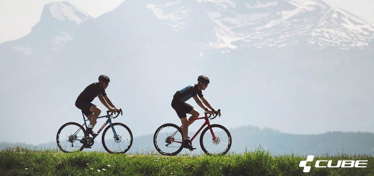 Due ciclisti pedalano in montagna in sella a biciclette da strada Cube dal catalogo 2020