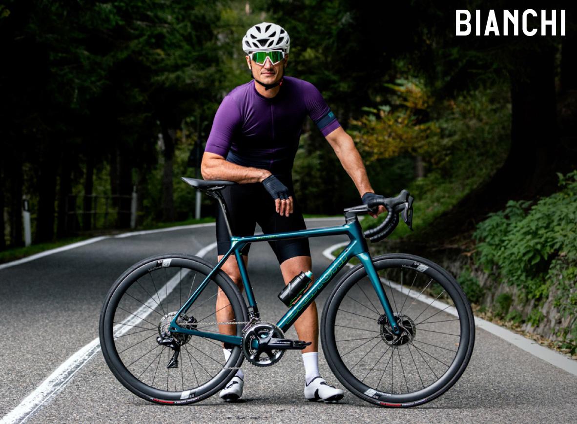 Ciclista posa insieme alla sua bicicletta Bianchi Specialissima Disc 2021