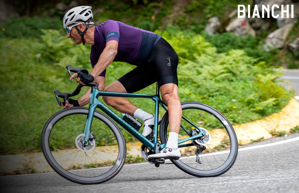 Un ciclista piega in curva in sella a una bici Bianchi Specialissima Disc 2021