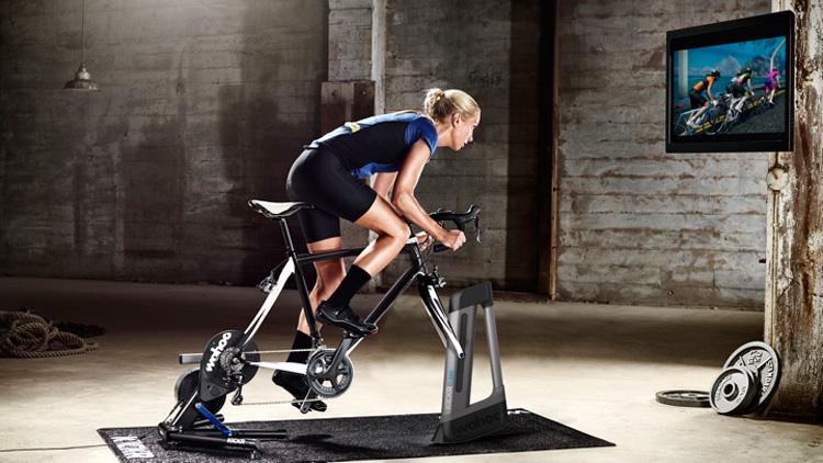 Una ciclista si allena in casa su un rullo Wahoo davanti alla TV