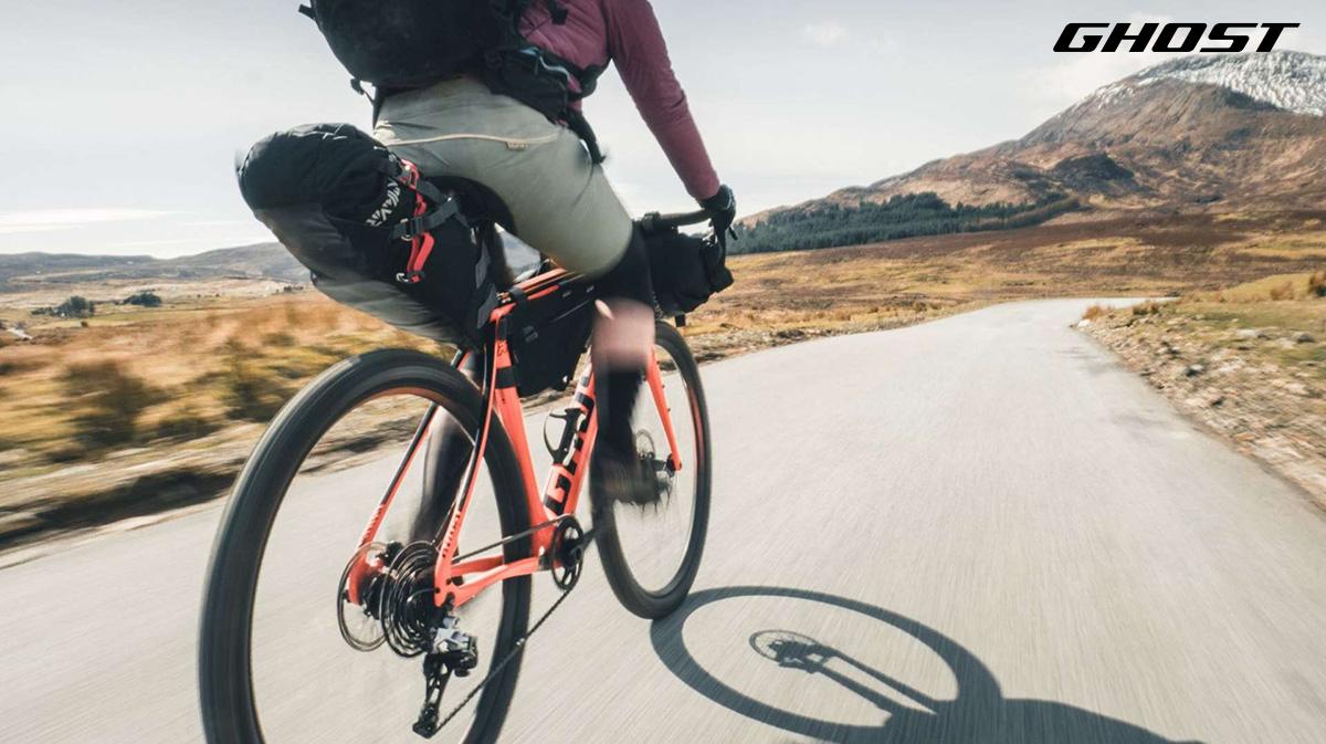 Un ragazzo pedala in sella alla sua bicicletta da strada Ghost equipaggiata con borse per bikepacking