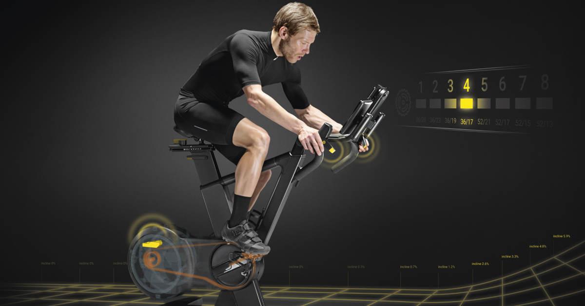 Un uomo si allena con la bici al chiuso