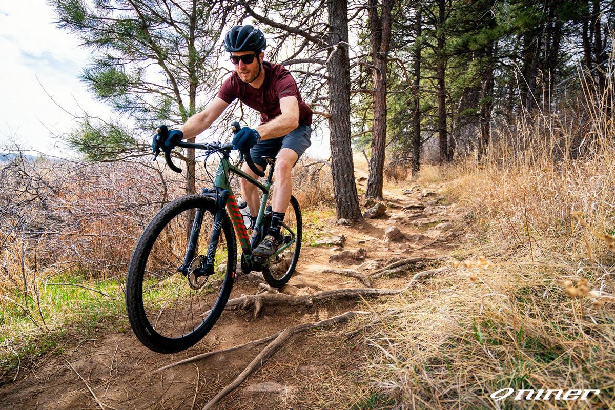 Ciclista pedala felice in sella a una bici Niner MCR 9 RDO 2021 su un sentiero di collina