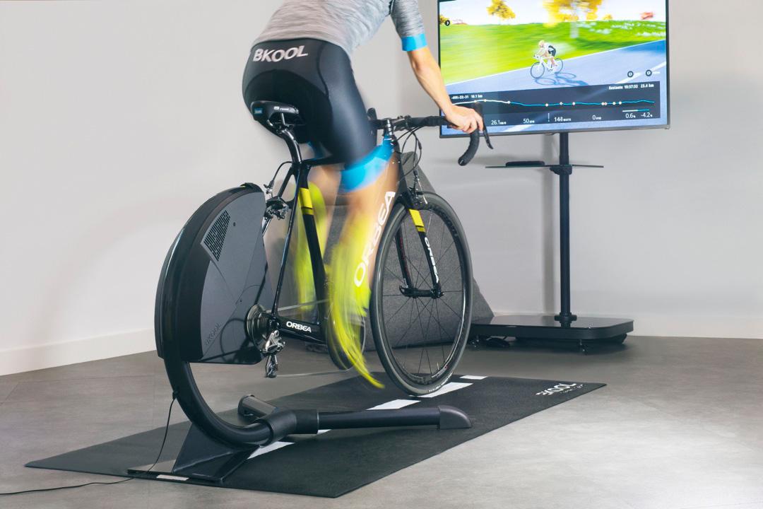 Un uomo si allena pedalando su un rullo indoor Bkool