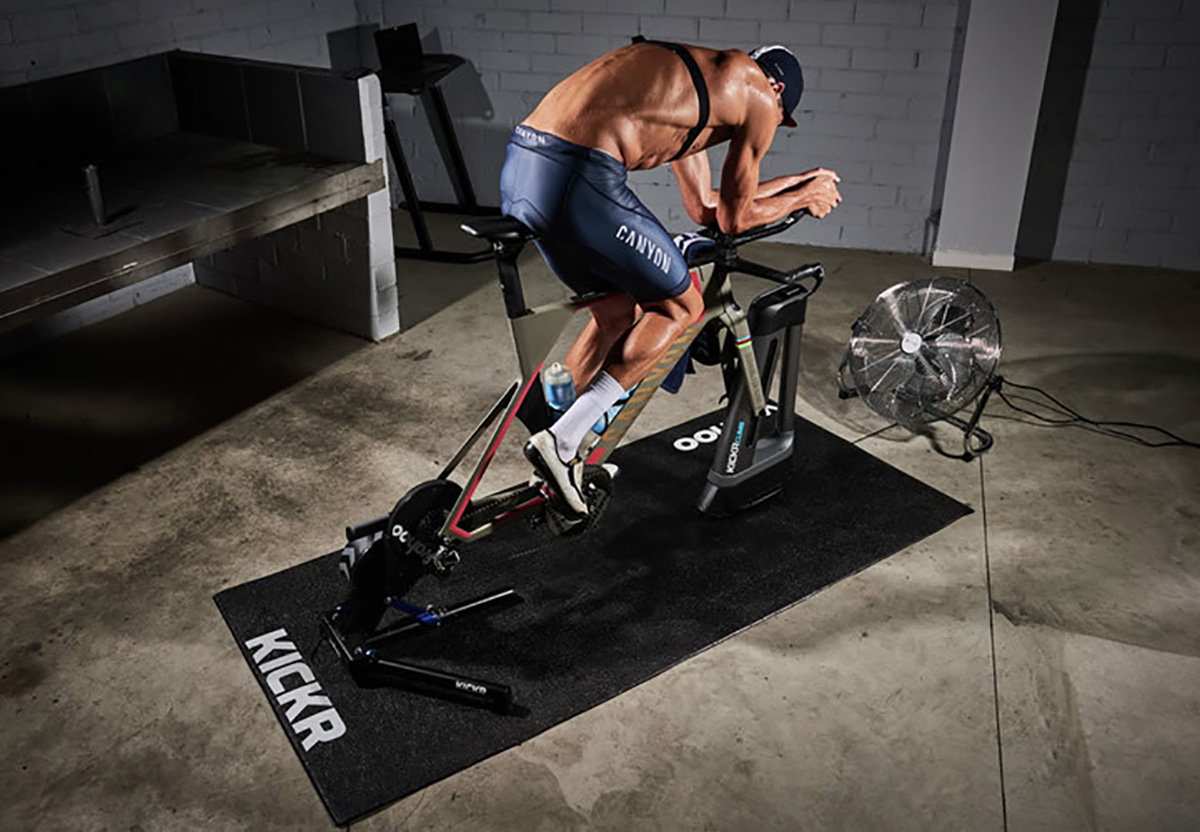 Un uomo si allena intensamente pedalando sui rulli indoor