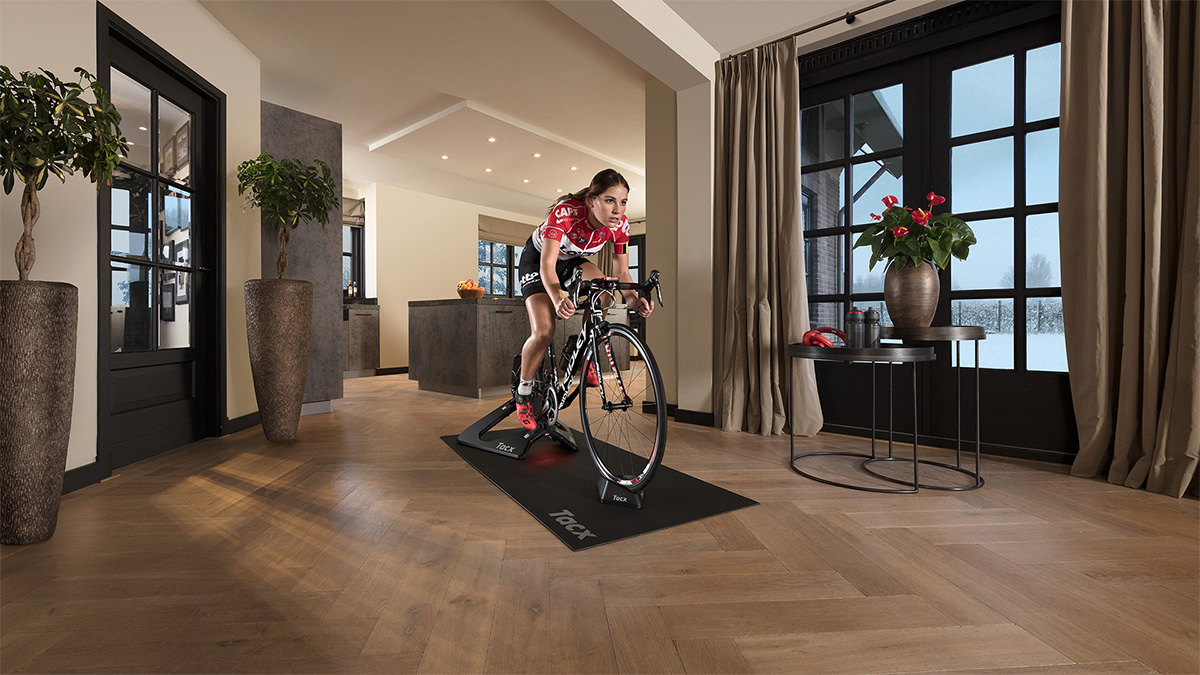 Una donna pedala in casa sui rulli da allenamento indoor Tacx