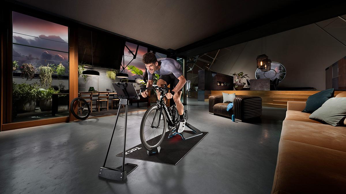Un uomo pedala in casa sui rulli da allenamento indoor Tacx