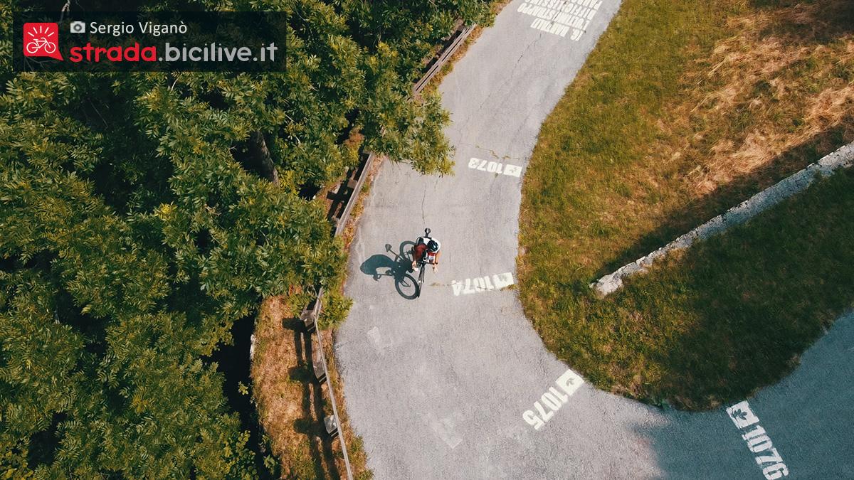 Sergio Viganò visto dall'alto del drone mentre pedala in una salita curva