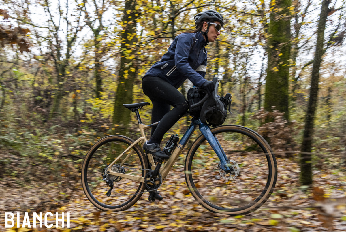 Una ciclista pedala nel bosco in sella a una bici gravel Bianchi Arcadex 2021