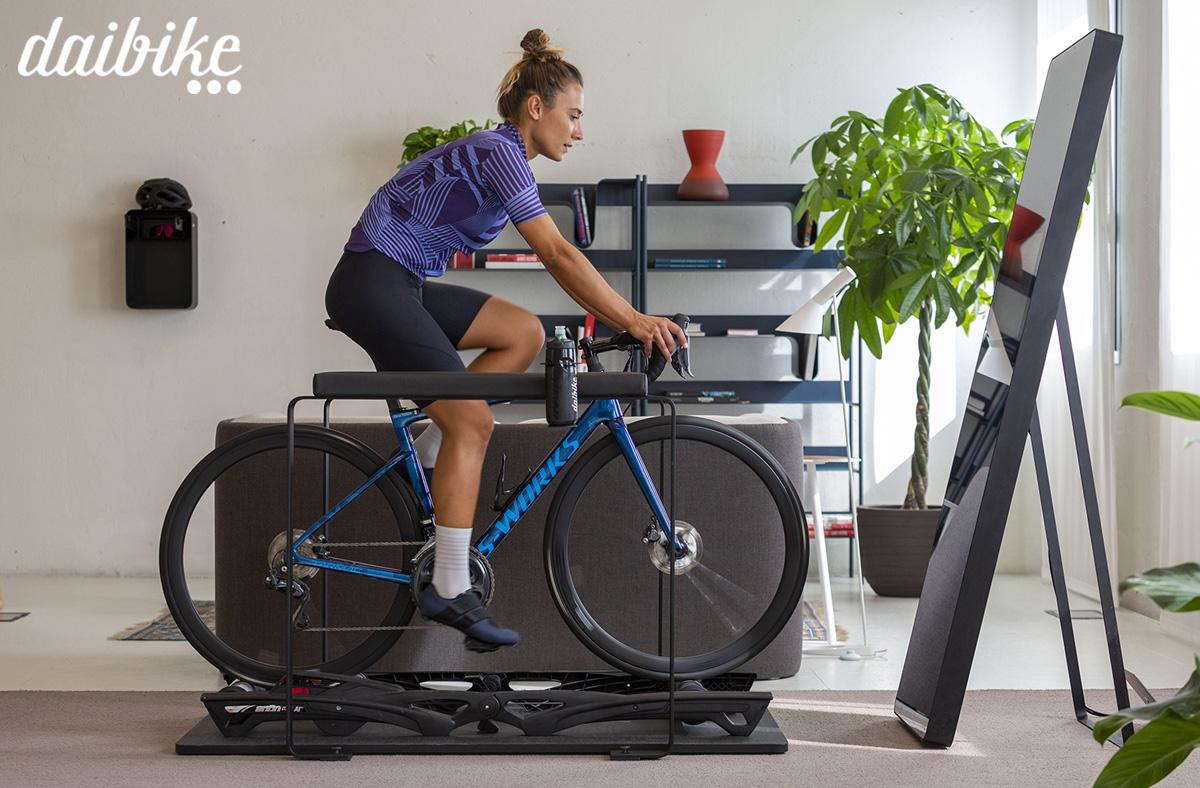 Ciclista donna si allena in casa utilizzando l'attrezzatura Daibike