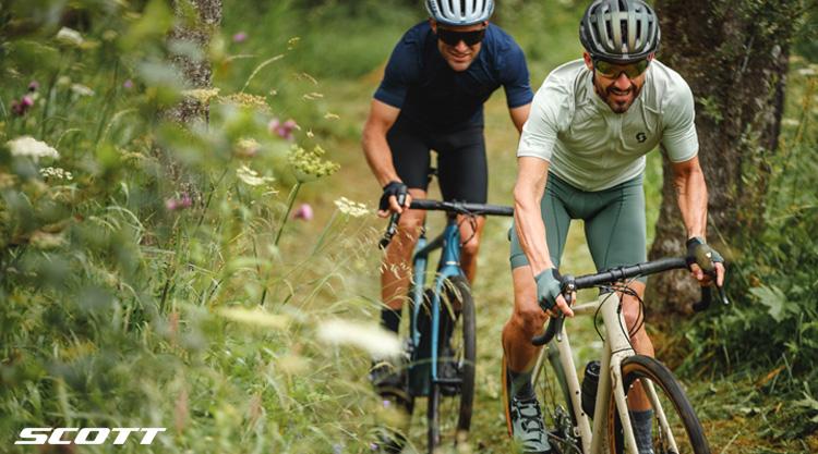 Due ciclisti pedalano sullo sterrato in sella a biciclette Scott Gravel/CX 2021