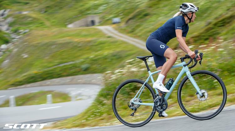 Una ciclista donna pedala in salita su una bici Scott Women's 2021