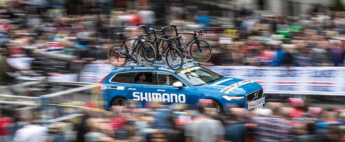 Un'auto dell'assistenza Shimano si muove tra la folla durante una gara ciclistica