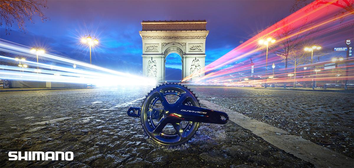 Una guarnitura Shimano posizionata al centro della strada con l'Arco di Trionfo di Parigi sullo sfondo