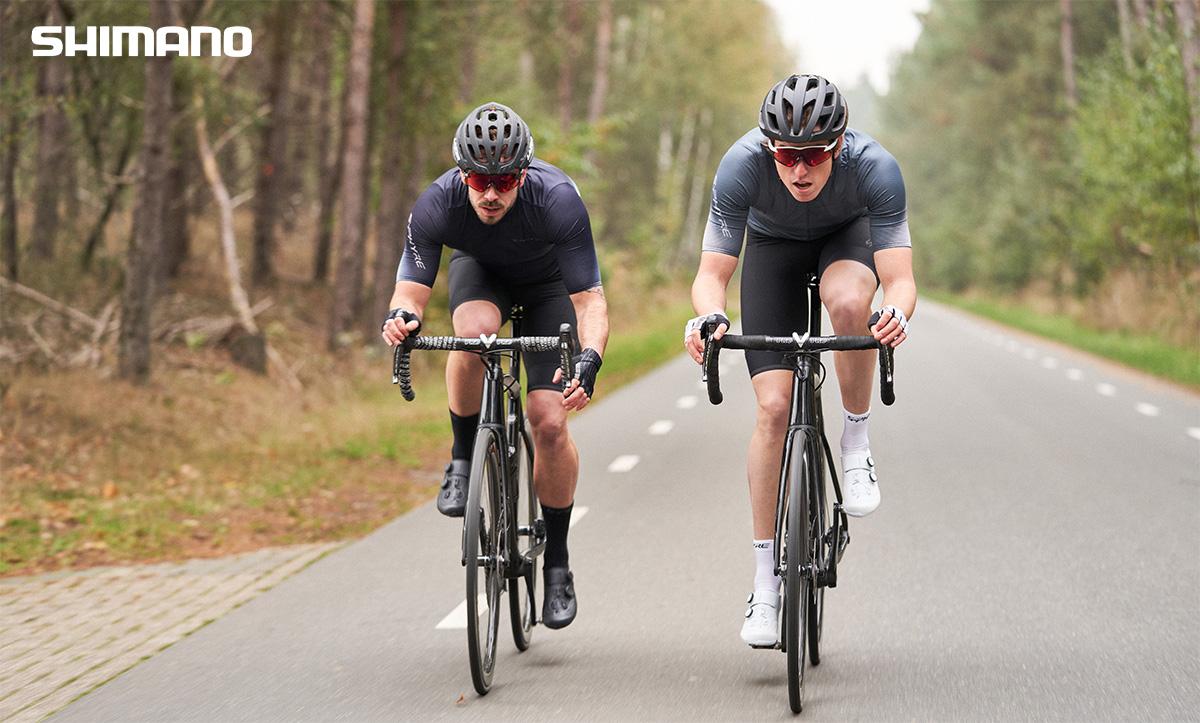 Due ciclisti pedalano sulle loro bici da corsa indossando i capi Shimano S-Phyre primavera/estate 2021