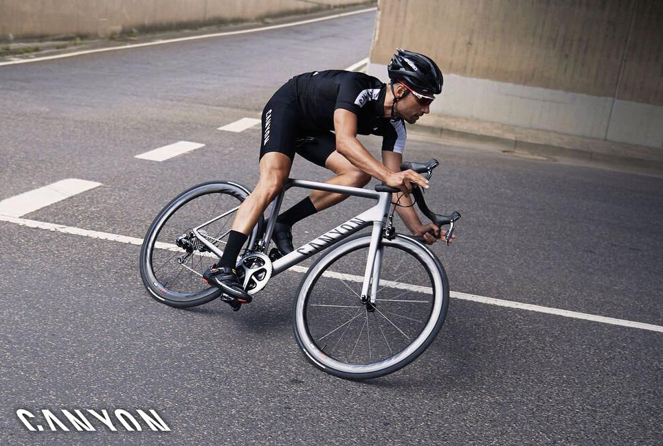 Un ciclista pedala su strada in sella ad una nuova bici da corsa Canyon 2021