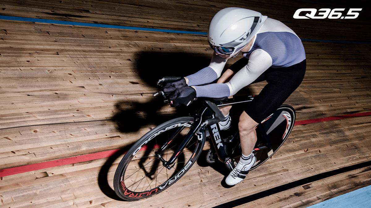 Un ciclista pedala su pista indossando l'abbigliamento tecnico Q36.5 2021