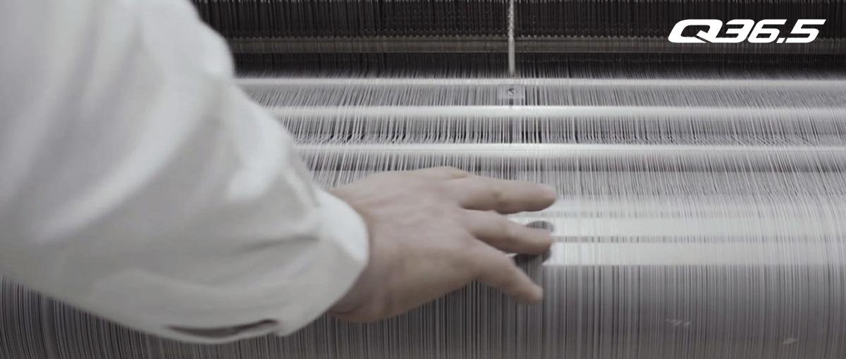 Un operaio della fabbrica di tessuti di Q36.5 alle prese con un macchinario per il filamento