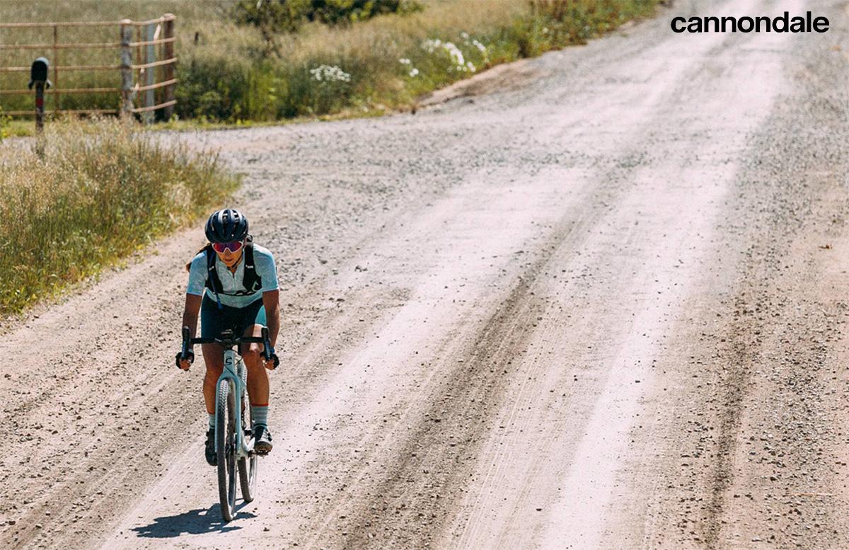 Una ciclista pedala su uno sterrato con la nuova bici da gravel Cannondale Supersix SE 2022