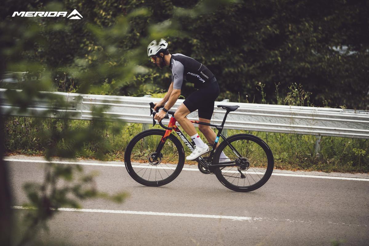Un ciclista pedala in salita sulla nuova bici da corsa Merida Scultura Team 2022