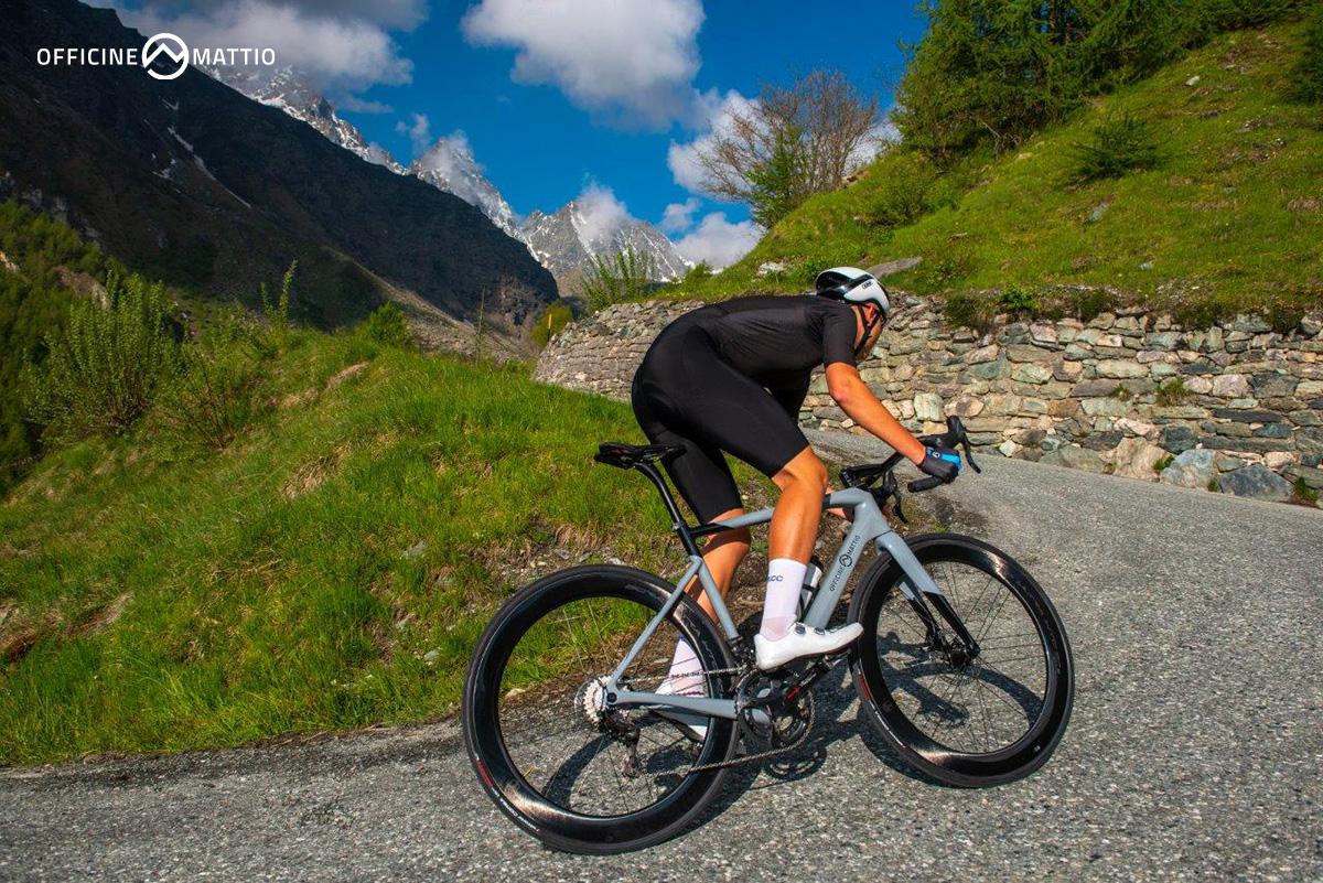 Un ciclista pedala su una strada in salita con la nuova bici da strada Officine Mattio OM1 S